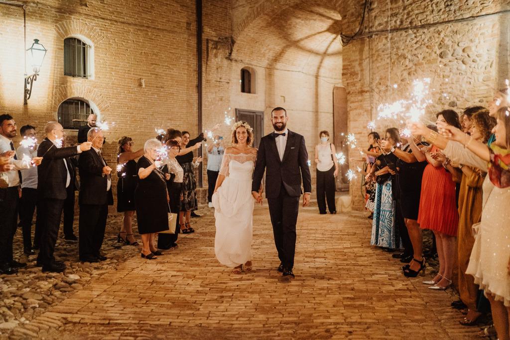 un lungo corridoio di invitati con in mano delle luminose stelle filanti accoglie gli sposi