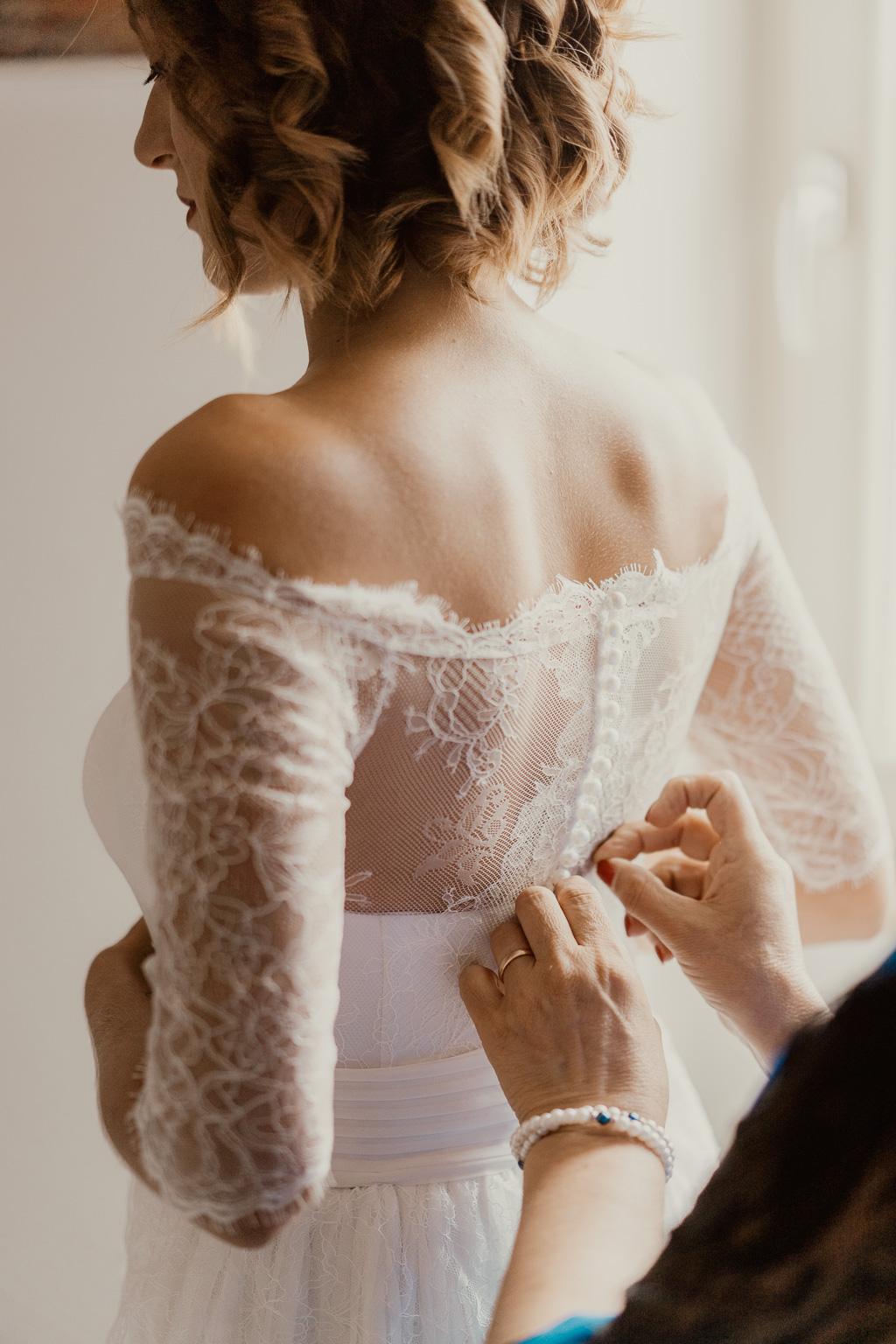 la sposa indossa l'abito in stile boho chic